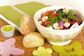 Fresh and healthy salad meal with tomotos red beans cheese toped with herbs buns napkins beside on table Stock Images