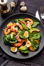 Fresh, healthy salad with shrimps, spinach and avocado on a blac Royalty Free Stock Photo