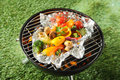 Fresh healthy selection of grilled vegetables cooked in foil over a bbq including broccoli peas onion sweet pepper mushroom and Royalty Free Stock Photo
