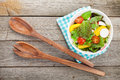 Fresh healty salad on wooden table and kitchen utensil view from above Stock Images