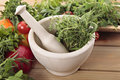 Fresh herbs with a mortar and pestle and vegetables Royalty Free Stock Photo