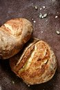 Fresh homemade bread from whole wheat and rye flour with flax seeds, pumpkin and oat flakes on a brown background. Royalty Free Stock Photo