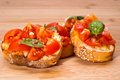 Fresh homemade bruschette crispy italian appetizer called bruschetta topped with tomato garlic and basil on wooden board Royalty Free Stock Photography
