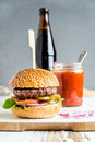 Fresh homemade burger on wooden serving board with spicy tomato sauce and bottle of dark beer, white background Royalty Free Stock Photo