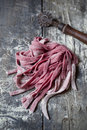 Fresh homemade pasta tagliatelle with beetroot on rustic wooden table Royalty Free Stock Photo