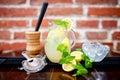 Fresh, iced mint lemonade in a jug with sliced lemon, mint