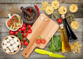 Fresh ingredients for cooking pasta tomato mushroom and spice spices over wooden table background with copy space Stock Photos
