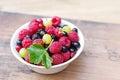 Fresh juicy berries, raspberries, currants, blackberries, a gooseberry in an white plate Royalty Free Stock Photo