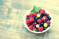 Fresh juicy berries, raspberries, currants, blackberries, a gooseberry in an white plate Royalty Free Stock Photo