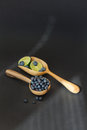 Fresh juicy blueberry fruits with limes on a wooden spoon against a dark background. Royalty Free Stock Photo