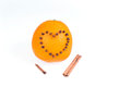 Fresh juicy bright orange decorated with a heart of cloves and vanilla sticks on a white background.