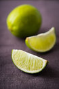 Fresh juicy limes on dark canvas background Royalty Free Stock Photo