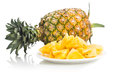 Fresh juicy nutritious cut pineapple with whole fruit as backgro Royalty Free Stock Photo