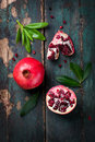 Fresh juicy pomegranate - whole and cut, with leaves on a wooden vintage background, top view, horizontal