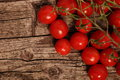 Fresh juicy red cherry tomatoes attached to the vine lying on a textured rustic wooden surface with copyspace overhead view Royalty Free Stock Photo