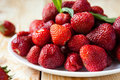 Fresh juicy strawberries on a white plate closeup Stock Photography