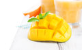 Fresh juicy summer cut mango, oranges and refreshment drinks on a wooden table on a white background, Royalty Free Stock Photo