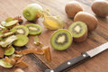 Fresh kiwi fruit being prepared for dessert closeup view of with a knife on a wooden kitchen counter Royalty Free Stock Images