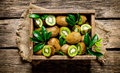 Fresh kiwi with leaves in an old box . Royalty Free Stock Photo