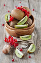 Fresh kiwi and redcurrant on the table Royalty Free Stock Images