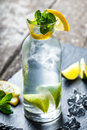 Fresh lemonade mojito with mint, lime and ice in glass on wooden background. Summer drinks and alcoholic cocktails Royalty Free Stock Photo