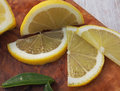 Fresh lemons on a cutting board placed on a wooden table. In the foreground one lemon cut in half. Royalty Free Stock Photo