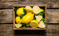 Fresh lemons in an old box with leaves. Royalty Free Stock Photo