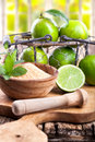 Fresh lime fruit in a wire basket with brown sugar on rustic wooden table Stock Photo