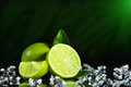 Fresh limes with leaves black background Royalty Free Stock Image
