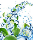 Fresh limes in water splash with ice cubes Royalty Free Stock Image