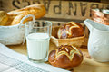 Fresh lye rolls in a wicker basket, a glass of milk, white pitcher on a wood table in a rustic style kitchen interior Royalty Free Stock Photo