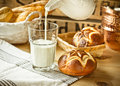 Fresh lye rolls in a wicker basket, process of pouring milk into a glass from pitcher, wood table, rustic style kitchen interior Royalty Free Stock Photo