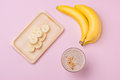 Fresh made banana smoothie in a glass on pink background Royalty Free Stock Photo