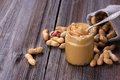 Fresh made creamy peanut butter in a glass jar and peanuts on old wooden table copy space Stock Photos