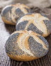 Fresh made poppyseed buns on dark wooden background Royalty Free Stock Images