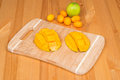 Fresh mango on a cutting board with Fresh Kumquats and a lime, on a wooden table Royalty Free Stock Photo