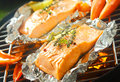 Fresh marine salmon grilling over a barbecue succulent steaks flavored with sprigs of thyme on aluminum foil with sweet pepper and Stock Image
