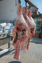 Fresh meat hanging being delivered to a butcher s shop from the delivery van Stock Photos