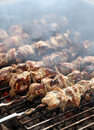Fresh meat on a steel skewer in a brazier smoke at Stock Photos