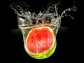 Fresh melon falling in water with splash on black Royalty Free Stock Photo