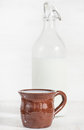 Fresh milk in ceramic mug and closed old fashioned bottle Royalty Free Stock Photo