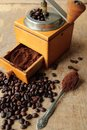 Fresh milled coffee grinder with beans on wooden table Stock Photo