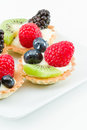 Fresh mini fruit tarts bite size with served on a white background Stock Photos