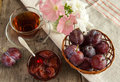 The fresh misted over plums in a wattled vase on an ancient wooden table with a bouquet of petunias in a vase Stock Photography