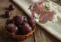 The fresh misted over plums in a wattled vase on an ancient wooden table with a bouquet of petunias in a vase Royalty Free Stock Photography