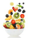 Fresh mixed fruit salad falling into a bowl of salad on white background Royalty Free Stock Photography