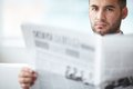 Fresh news a young serious businessman with newspaper looking at camera Royalty Free Stock Photo