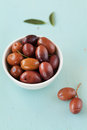 Fresh olives in white bowl on wooden table rustic Stock Images