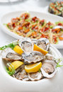 Fresh opened oysters and another dishes on restaurant table Stock Photo