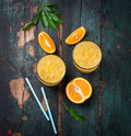 Fresh orange juice with crushed ice and fresh oranges and blue straws on an old vintage exotic background Royalty Free Stock Photo
